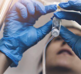 Nurse with blue gloves adjusting IV